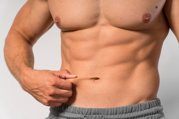 Vista frontale dell'uomo senza camicia in forma che mostra gli addominali Foto Gratuite