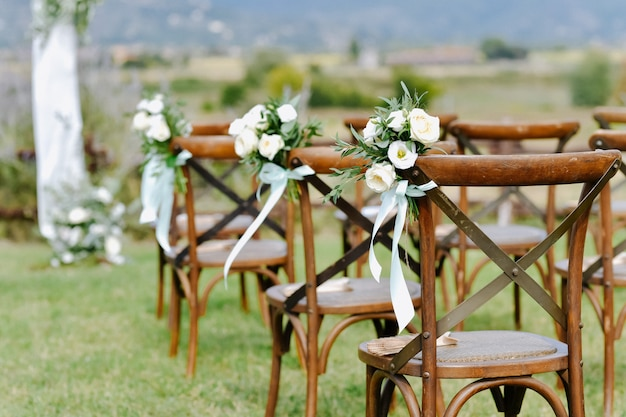 Front view of floral decoration from white eustomas and ruscus of brown chiavari chairs outdoors Free Photo