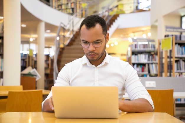 Front view of focused young man typing on laptop at library Free Photo