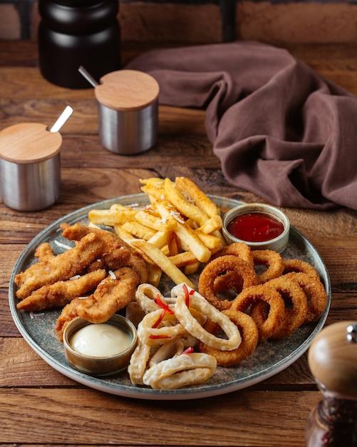 Una vista frontale patatine fritte con ali di pollo fritte e anelli di cipolla con ketchup sulla patata pasto cibo scrivania in legno marrone Foto Gratuite