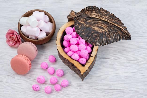 Una vista frontale francese macarons insieme a marshmallow e rosa, caramelle su bianco, zucchero candito biscotto dolce Foto Gratuite