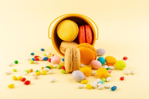 Una vista frontale francese macarons deliziosi e caramelle di zucchero biscotto torta al forno Foto Gratuite