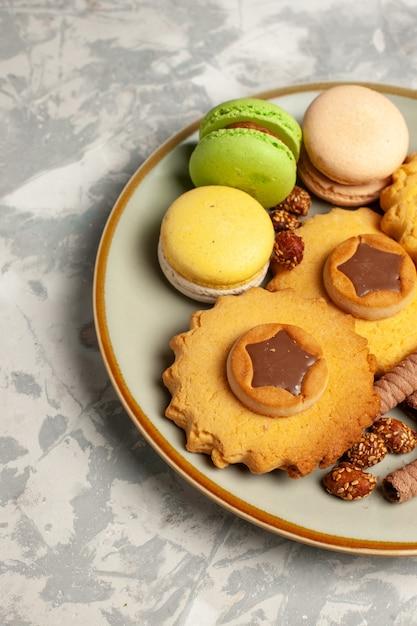 白い表面にケーキとクッキーの正面図フレンチマカロン 無料写真