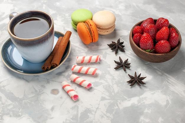 白い表面のケーキシュガービスケット甘いクッキーにお茶と新鮮な赤いイチゴの正面図フレンチマカロン 無料写真