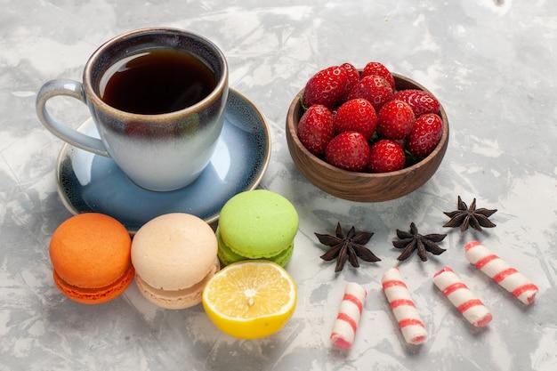 正面図白い机の上のお茶のカップとフランスのマカロンケーキビスケットシュガーパイ甘いクッキー 無料写真