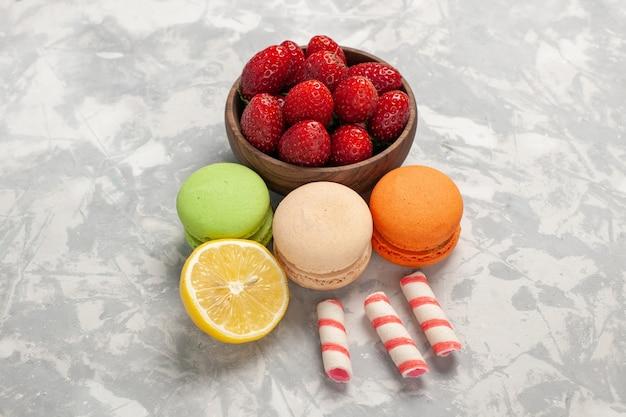 Macarons francesi di vista frontale con le fragole fresche sullo zucchero dolce del biscotto della torta della bacca dei frutti di superficie bianca Foto Gratuite