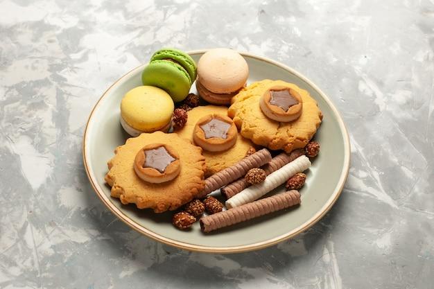 Вид спереди французские макароны с маленькими пирожными и печеньем на белой поверхности Бесплатные Фотографии