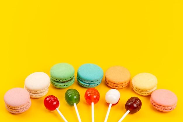 Una vista frontale francese macarons con lecca-lecca su giallo, torta di zucchero candito Foto Gratuite