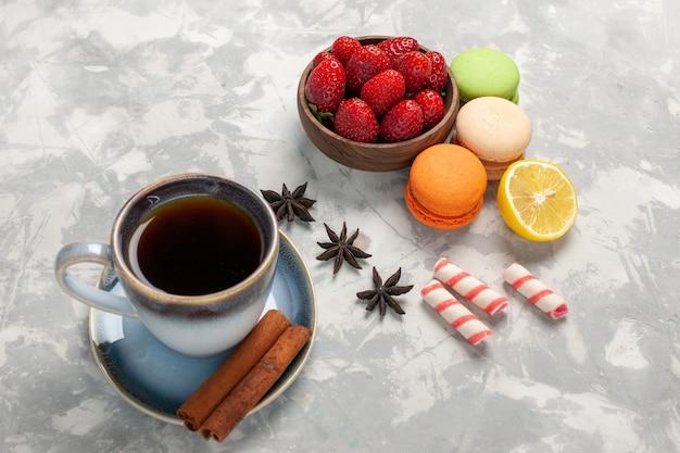 正面図フレンチマカロンとティーシナモンと白い表面の新鮮なイチゴフルーツベリーケーキビスケットスイート 無料写真