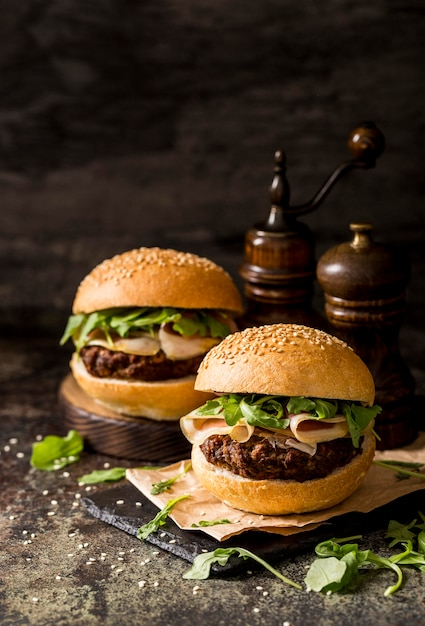 Front view fresh beef burgers with bacon on slate board Free Photo