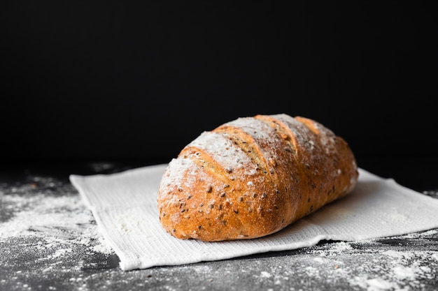 Front view fresh bread on black background and cloth with flour Free Photo