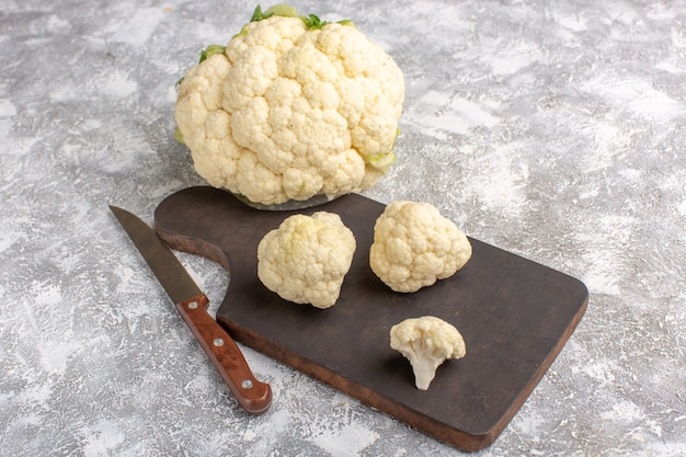 Front view of fresh cauliflower with knife and on the light-white wall Free Photo