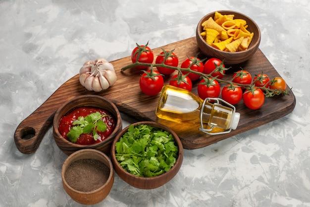 Свежие помидоры черри с приправами и зеленью на белой поверхности, вид спереди, здоровый салат Бесплатные Фотографии