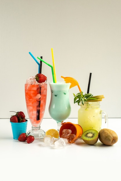 Cocktail freddi freschi di una vista frontale dentro i vetri con le paglie con la frutta fresca isolata su bianco Foto Gratuite