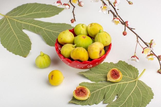Вид спереди свежий инжир, сладкие и вкусные плоды внутри красной тарелки на белом столе Бесплатные Фотографии