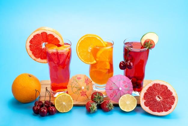 Una vista frontale cocktail di frutta fresca con fette di frutta fresca raffreddamento a ghiaccio sul blu, bere succo di frutta cocktail di colore Foto Gratuite