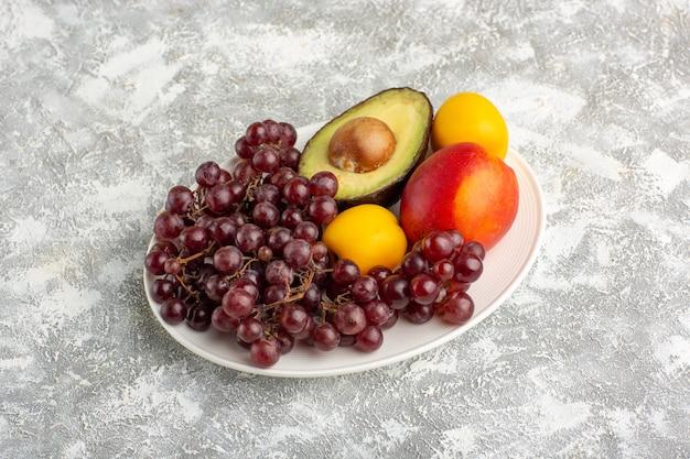 Vista frontale frutta fresca uva pesca e avocado all'interno della piastra sulla superficie bianca Foto Gratuite