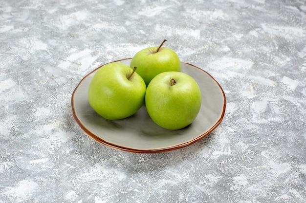 Вид спереди свежие зеленые яблоки внутри тарелки на белой поверхности свежие спелые спелые фрукты пищевой витамин Бесплатные Фотографии