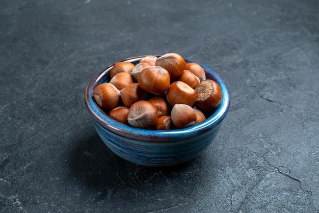 Front view fresh hazelnuts inside little pot on dark surface Free Photo