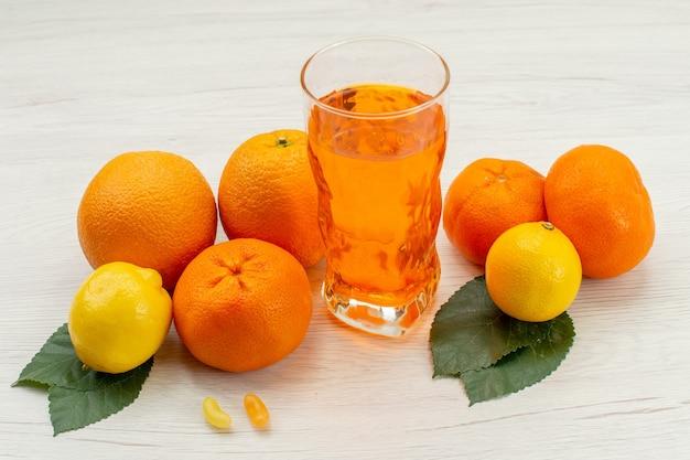 Vista frontale succo d'arancia fresco con arance e agrumi sulla scrivania bianca Foto Gratuite