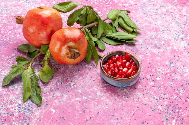 Front view fresh pomegranate with green leaves on pink surface Free Photo