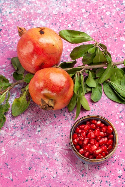 Front view fresh pomegranate with green leaves on the pink surface Free Photo