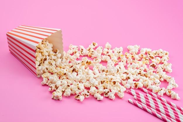 Un popcorn fresco di vista frontale salato si è diffuso tutto sul seme di mais rosa, spuntino di film Foto Gratuite