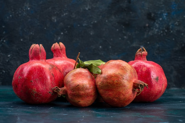 Front view of fresh red pomegranates on dark surface Free Photo