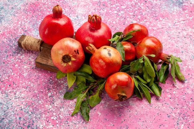 Вид спереди свежие красные гранаты с зелеными листьями на розовой поверхности Бесплатные Фотографии