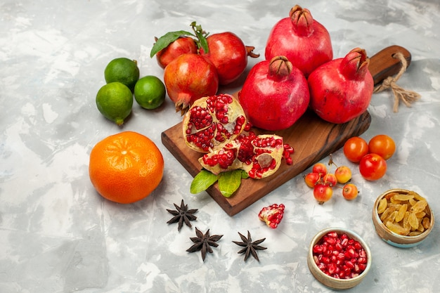 Front view fresh red pomegranates with tangerines and plums on the light-white desk Free Photo