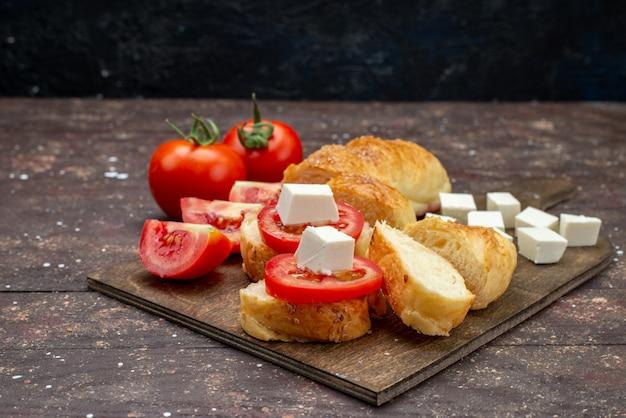 正面の新鮮なおいしいパンの長いパンが形成された茶色のチーズとトマトのカットペストリー 無料写真