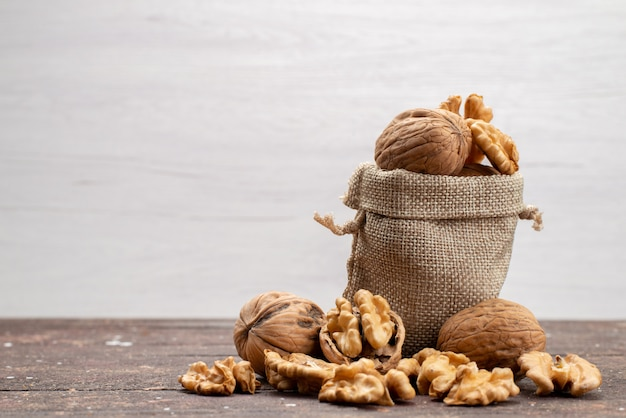 Front view fresh whole walnuts in shells and cleaned up on grey, nut walnut snack Free Photo