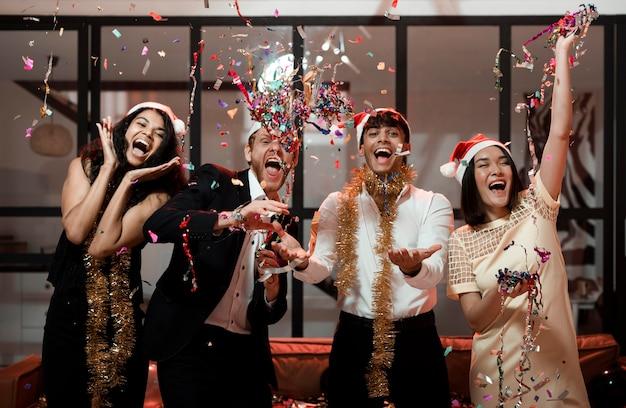 Друзья вид спереди празднуют новогоднюю вечеринку Бесплатные Фотографии