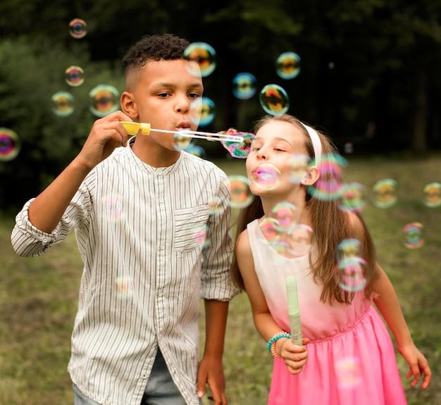 Vista frontale di amici che fanno bolle di sapone Foto Gratuite