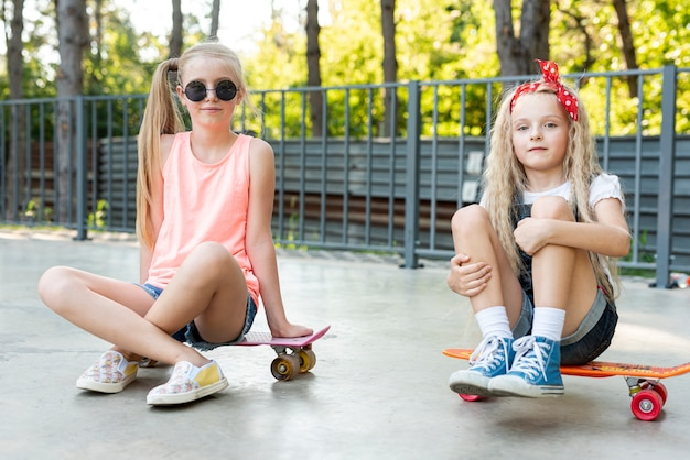 Front view of friends sitting on skateboards Free Photo