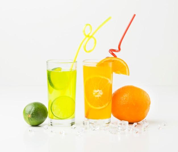Vista frontale del succo di frutta in bicchieri con cannucce Foto Gratuite
