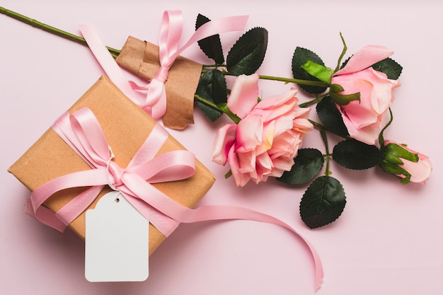 Front view of gift box with rose bouquet and ribbon Free Photo
