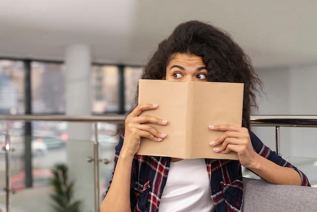 本で彼女の顔を覆っている正面少女 無料写真