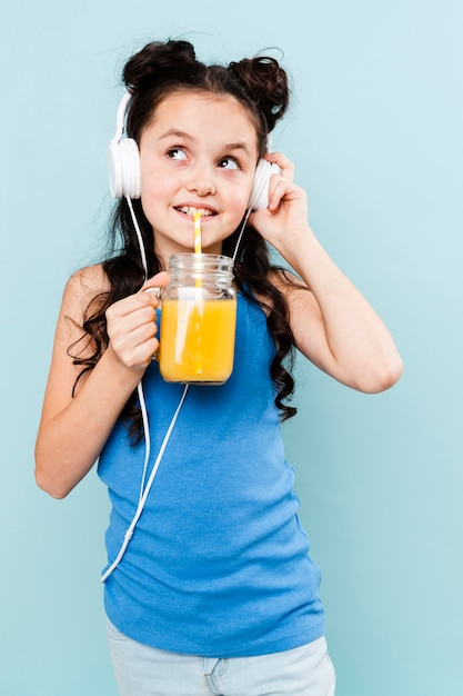 Front view girl drinking juice and listening music Free Photo