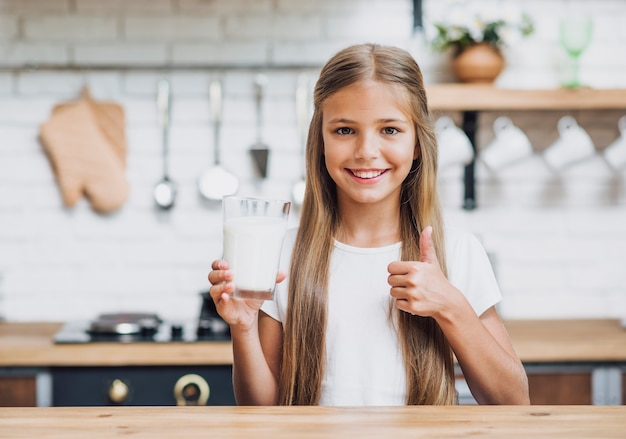 Front view girl holding a glass of milk Free Photo