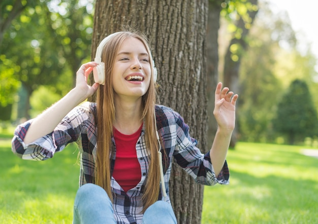 Front view girl listening to music outdoors Free Photo
