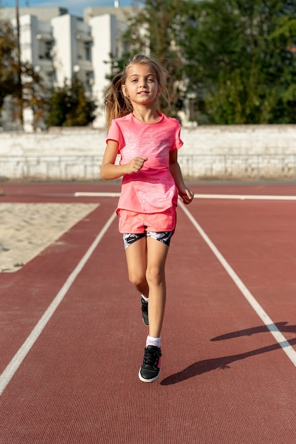 Front view of girl in pink t-shirt running Free Photo