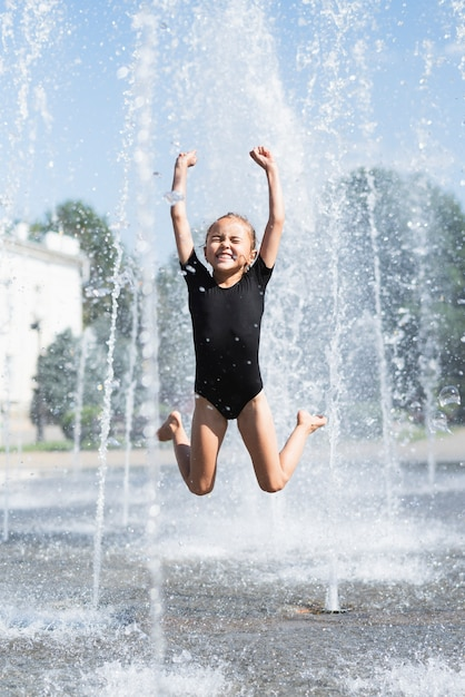 Front view of girl playing at fountain Free Photo