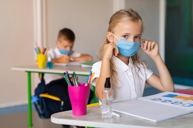 クラスで彼女の医療マスクを置く正面図少女 無料写真