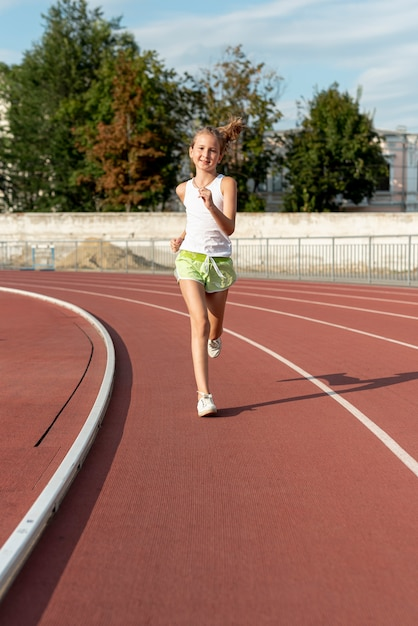 Front view of girl on running track Free Photo