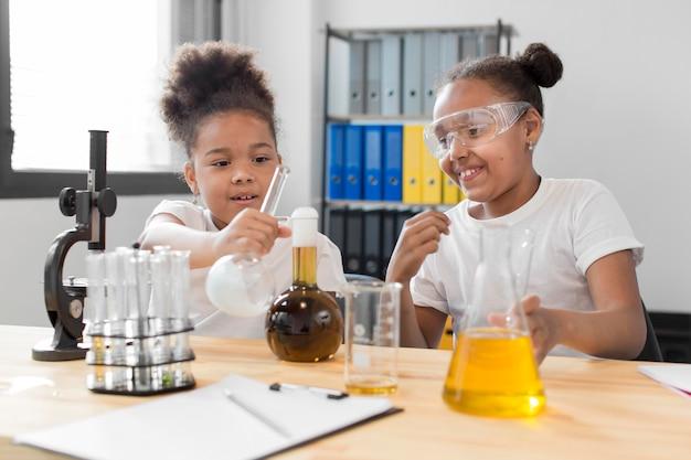 Vista frontale dello scienziato della ragazza che sperimenta con la chimica a casa Foto Gratuite