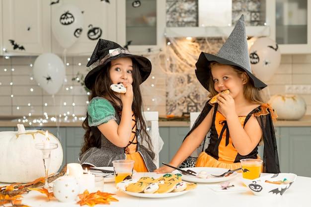 Vista frontale delle ragazze che mangiano i biscotti di halloween Foto Gratuite