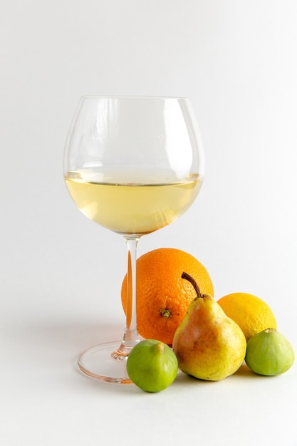 Front view glass of wine white wine with fresh fruits on light white desk drink alcohol bar water fruits Free Photo