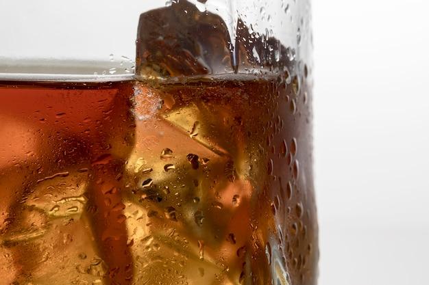 Vista frontale del vetro con liquido e ghiaccio Foto Gratuite
