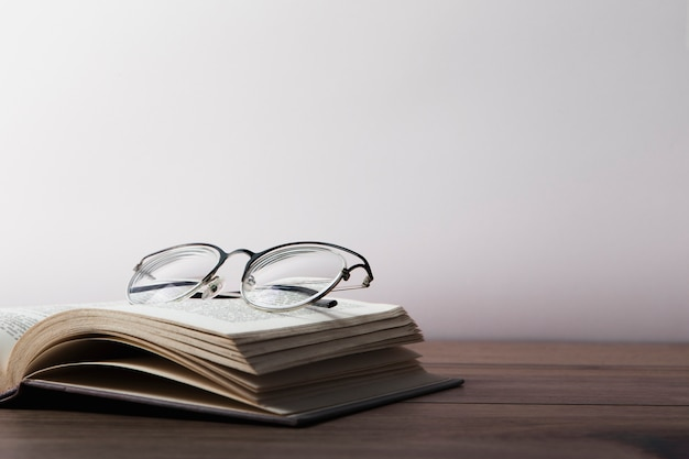 Front view of glasses on open book on wooden table Premium Photo